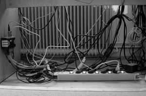 Umschalter, Steckerleiste und viele, teilweise gebündelte Kabel unter einem Schreibtisch